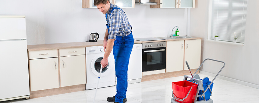 Young Happy Worker In Overall Mopping Floor