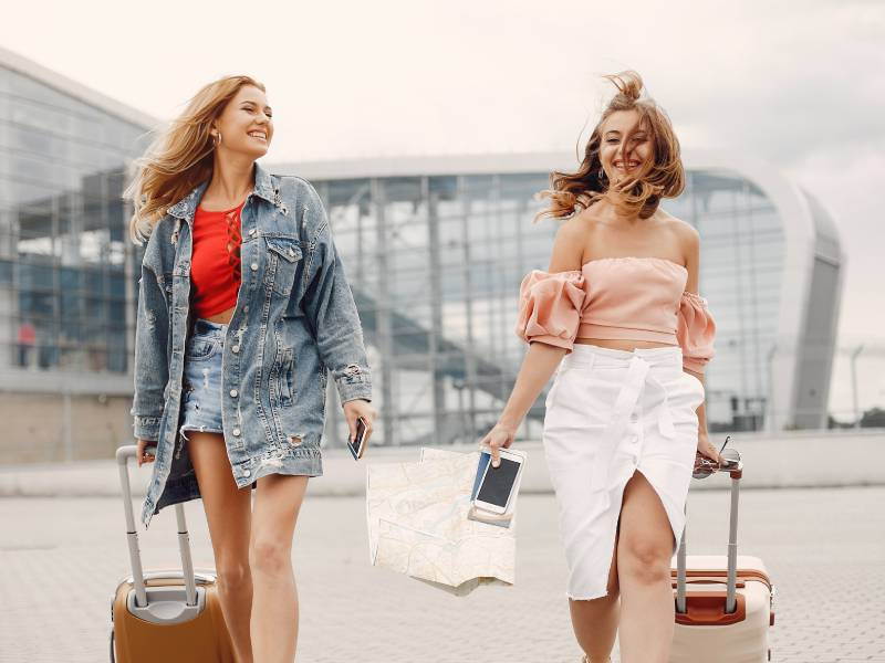 two girls with suitcases walking