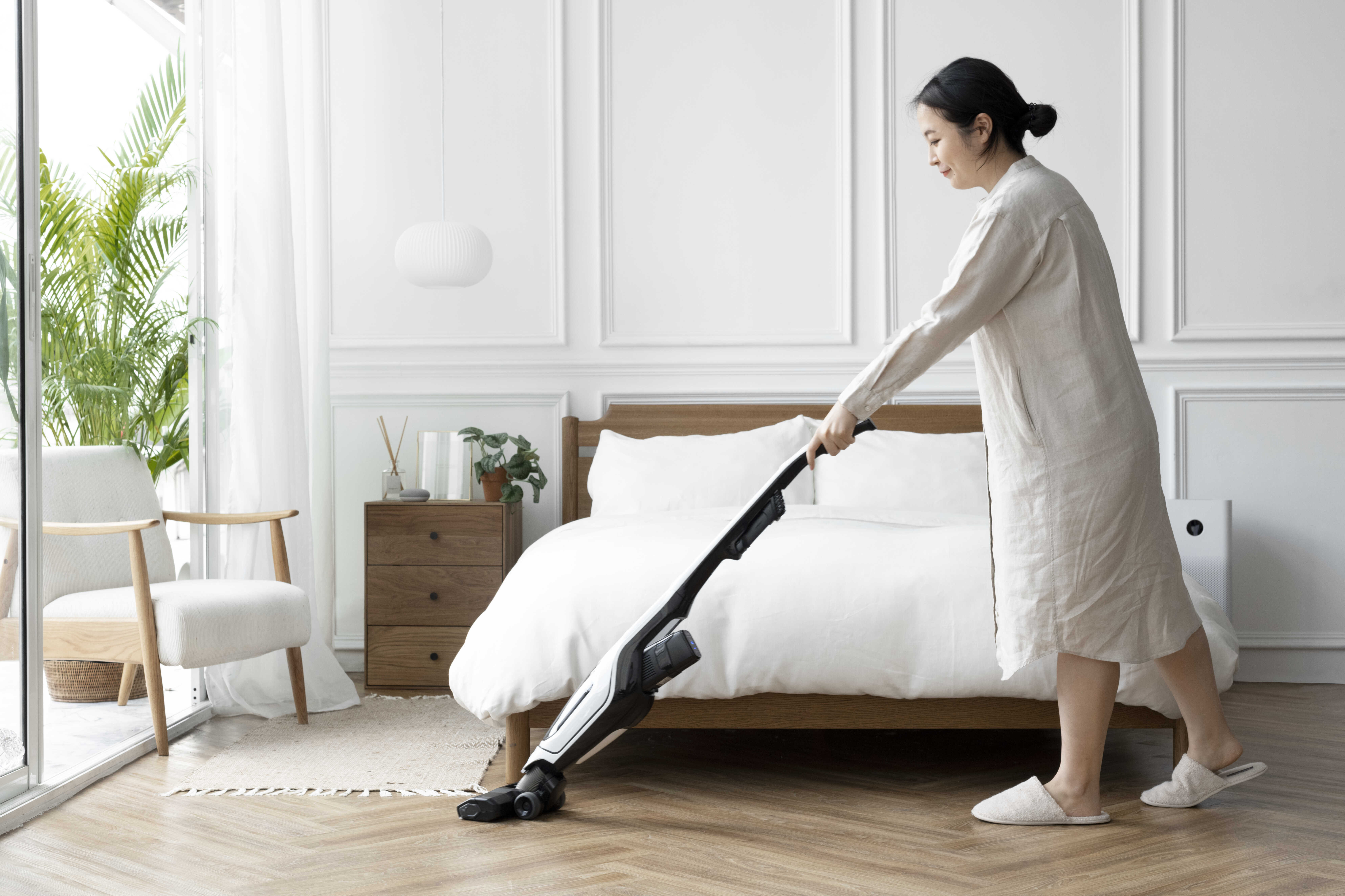 Woman cleaning bedroom